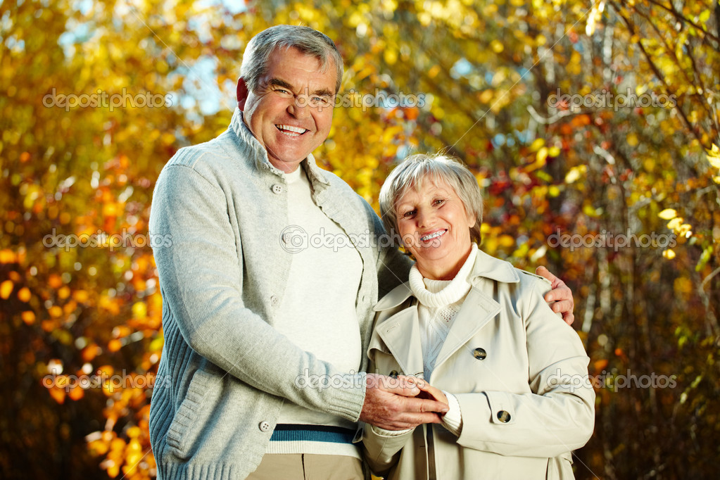 Photo of happy aged man and woman looking at camera in autumnal park  Stock Photo #11672421