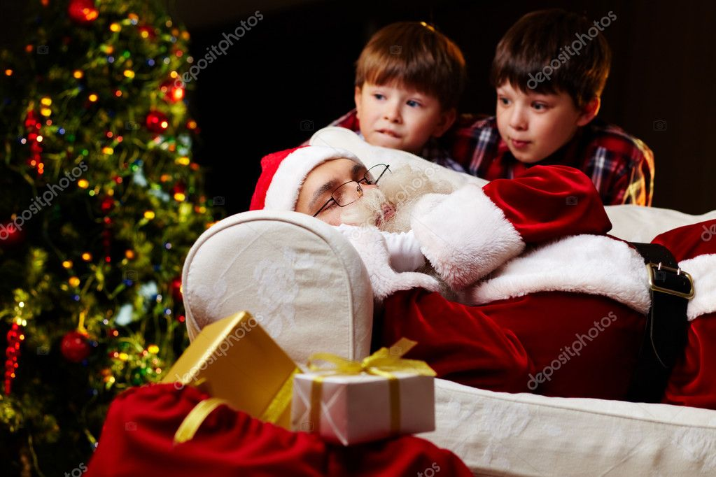 Photo of Santa Claus sleeping on sofa with two amazed kids near by — Stock Photo #11672638