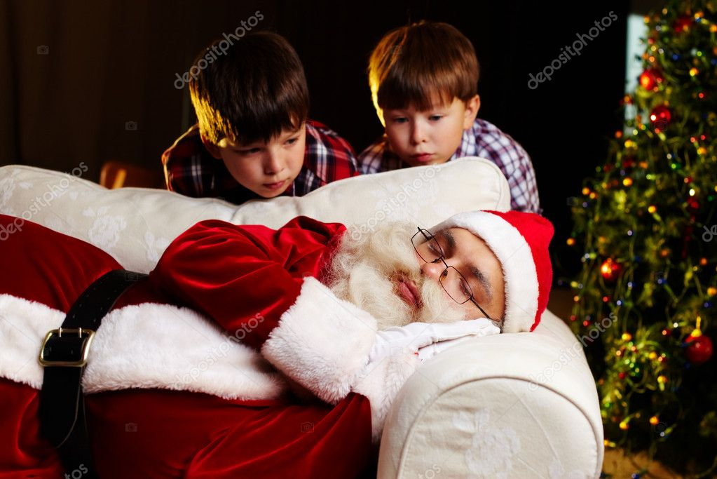Photo of Santa Claus sleeping on sofa with two amazed kids looking at him — Stock Photo #11672642