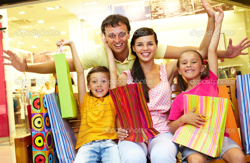 Portrait of joyful family sitting in store with plenty of shopping bags  Stock Photo #11673881