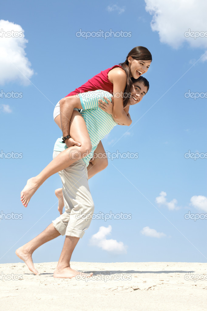 A young man carrying a woman on back — Stock Photo #11675404