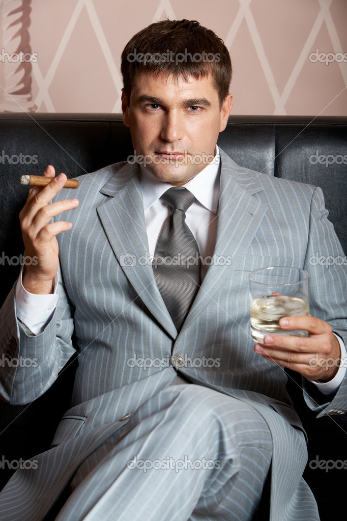 Portrait of handsome man in grey suit sitting on leather sofa with whisky and cigar in casino — Stock Photo #11676416
