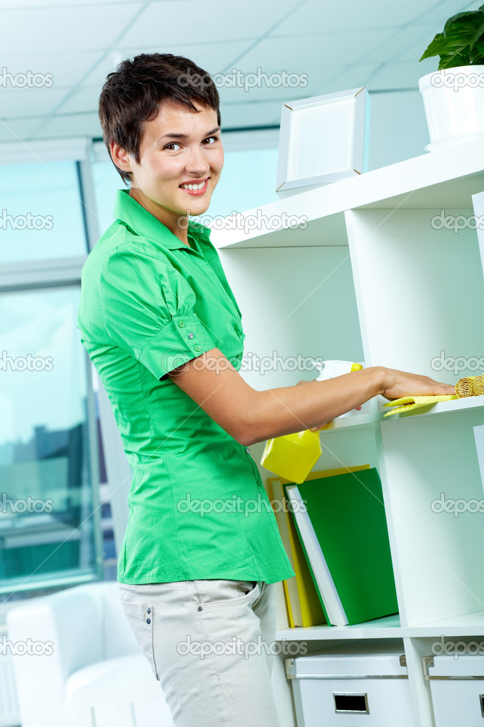 Photo of young woman dusting and looking at camera — Stock Photo #11691300