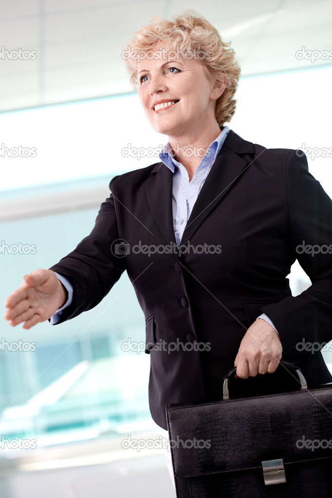 Portrait of smiling middle aged businesswoman with briefcase giving her hand for a handshake — Stock Photo #11692205