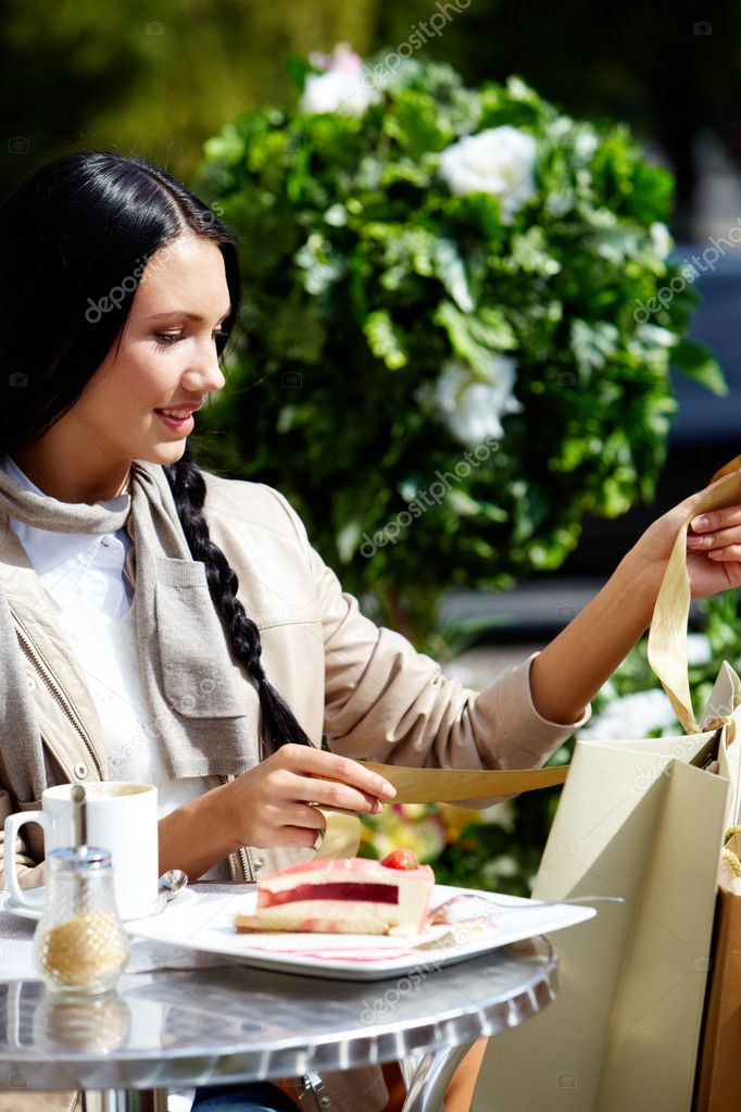 Image of happy female in open air cafe looking at paperbags in urban environment — Stock Photo #11693981