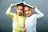 Twins under book — Stock Photo