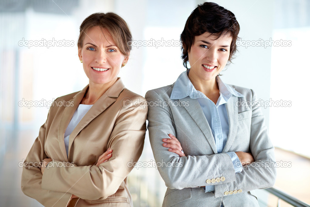 Portrait of two strong women in business standing shoulder to shoulder expressing unity — Stock Photo #12497947