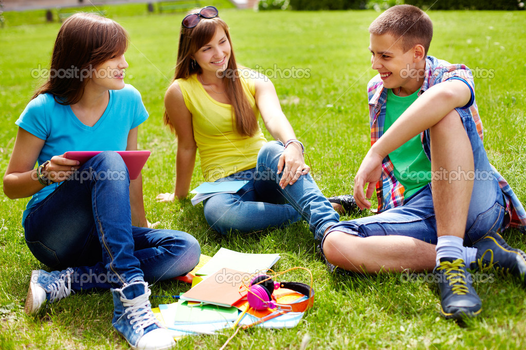 Cute high-school students doing homework outdoor on the lawn — Stock Photo #12502039