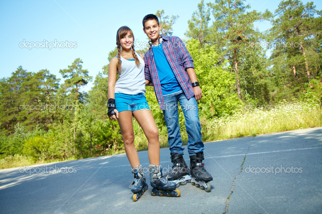 Summer portrait of happy teens roller skating in park — Stock Photo #12509600