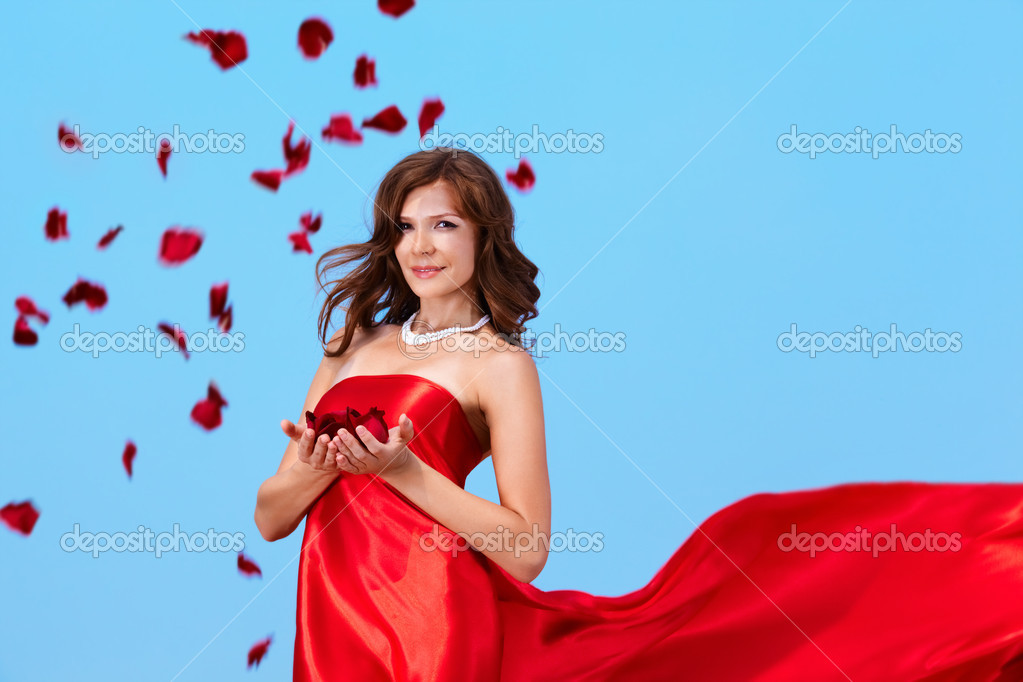 Portrait of charming female in elegant red dress holding rose petals  Stock Photo #12510334