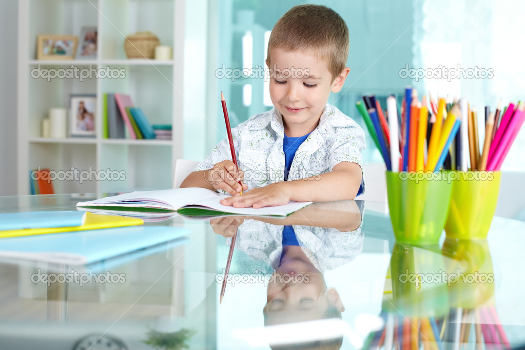 Happy schoolkid drawing with multicolored pencils  Stock Photo #12514503