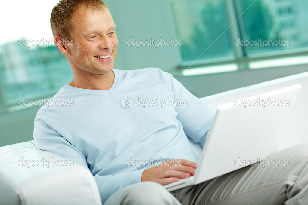Smiling man using his laptop to surf the internet — Stock Photo #12514568