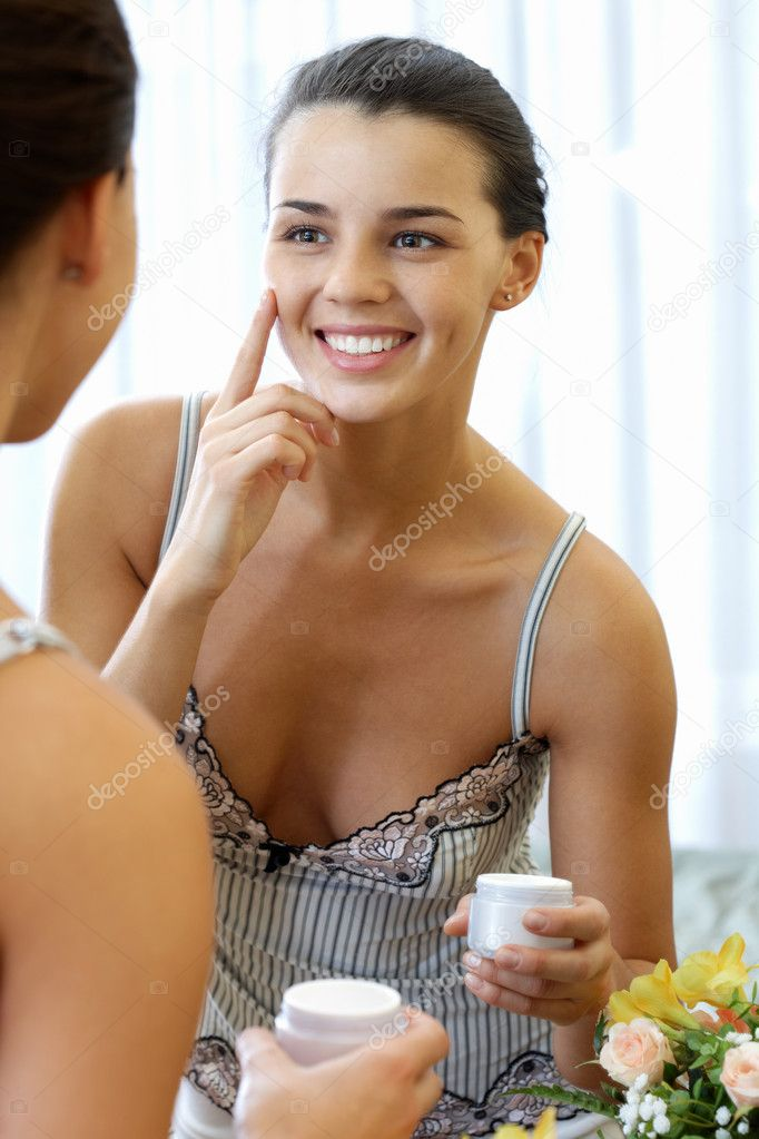 Portrait of pretty female applying cream onto her face and smiling — Stock Photo #12516736