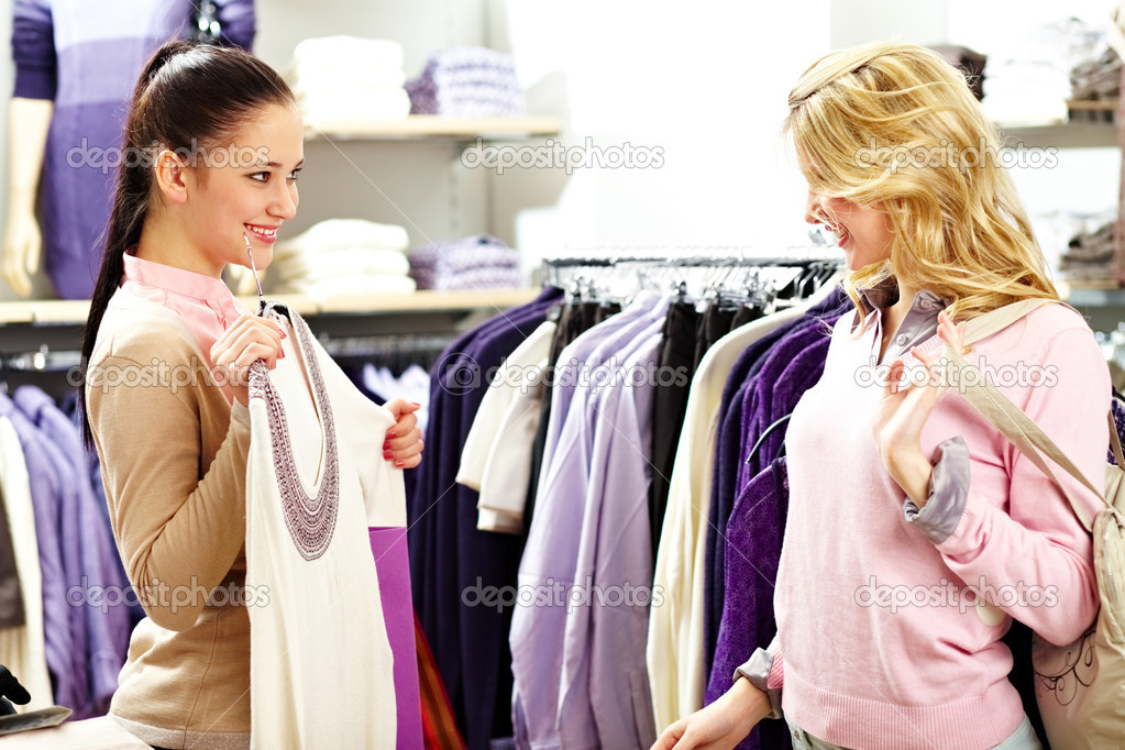 Image of two pretty girls choosing clothes from new collection in department store — Stok fotoğraf #12521975
