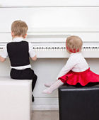 Childer playing the piano — Stock Photo