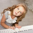 Beautiful blond little girl in pretties sitting near piano — Stock Photo #11670643