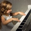 Blond girl playing a piano - Stock Photo