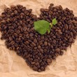 Heart composed of coffee and green leafage — Photo