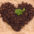 Heart composed of coffee and green leafage - Stok fotoğraf
