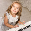 Little girl sitting near the piano — Stock Photo