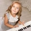 Little girl sitting near the piano — Stock Photo