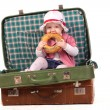 Little girl in suitcase eating bread — Stock Photo #12150372