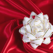 White gift bow on an elegance red silk background — Stock Photo