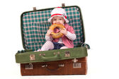 Little girl in the suitcase eating bread — Stock Photo