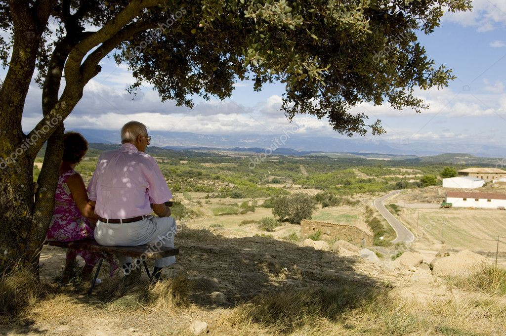 Old couple sitting on a bench, watching at the landscape — Stock Photo #10861542