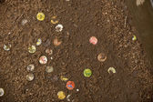 Discarded soda caps in ground, Tanzania, Africa — Stock Photo