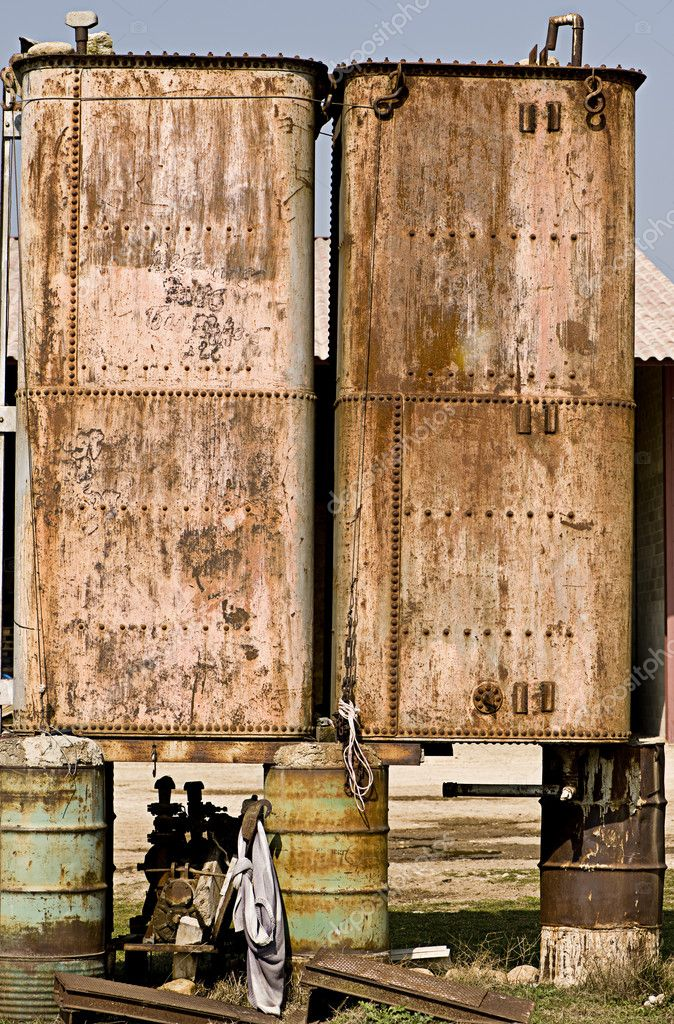 Rusted metal tanks balanced on oil drums — Stock Photo #10888693