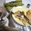 Chihuahua standing on hind legs to look at leftover meal on dinner table — Stock fotografie