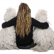 Rear view of two White Corded standard Poodles and a girl with dreadlocks sitting in front of white background - Stockfoto