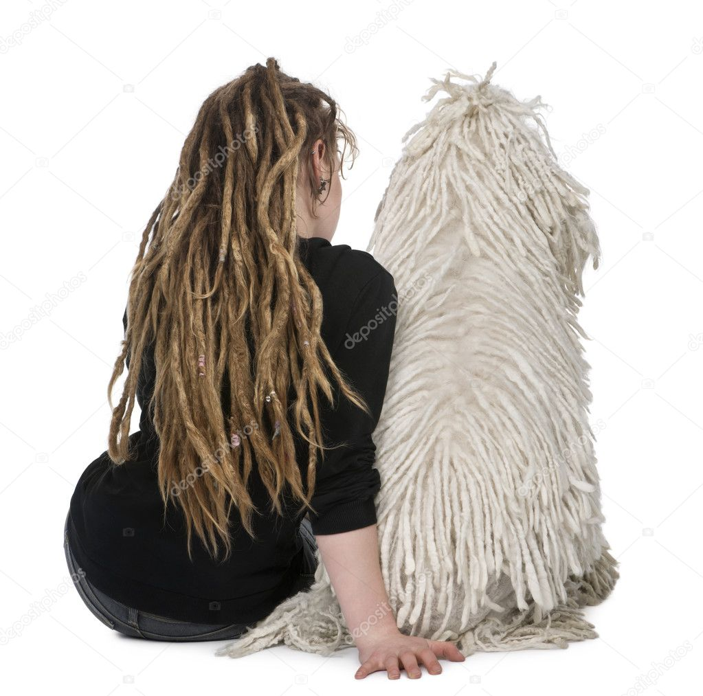Rear view of a White Corded standard Poodle and a girl with dreadlocks sitting in front of white background — Stock Photo #10890750