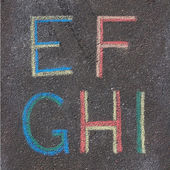 Alphabet letters drawn on asphalt with chalk, e, f, g, h, i — Stock Photo