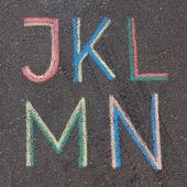 Alphabet letters drawn on asphalt with chalk, j, k, l, m, n — Stock Photo
