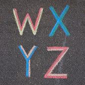 Alphabet letters drawn on asphalt with chalk, w, x, y, z — Stock Photo