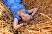Beautiful girl lies in wheat — Stock Photo