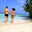 Loving couple walking on a tropical beach — Stock Photo #10965788