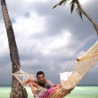 Handsome man chatting to woman in hammock — Stock Photo #10965922