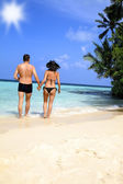 Loving couple walking on a tropical beach — Stock Photo