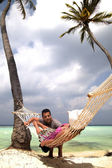 Handsome man chatting to woman in hammock — Stock Photo