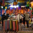Stock Photo: Buyers in colored fabric shop in Fes