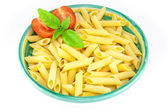 Bowl full of pens pasta with tomatoes and basil — Stock Photo