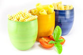 Fusilli, rigatoni and pens pasta in a green, blue and orange jar — Stock Photo