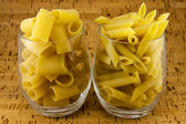 Two varieties of pasta inside two transparent glasses — Stock Photo