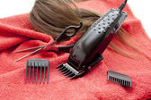 Black electric clippers with red towel — Stock Photo