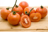 Fresh tomatoes on wooden board — Stock Photo