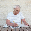 Elderly man with a crossword puzzle — Stock Photo