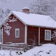 Small snowy cottage in Smaland (Sweden) - Stock Photo